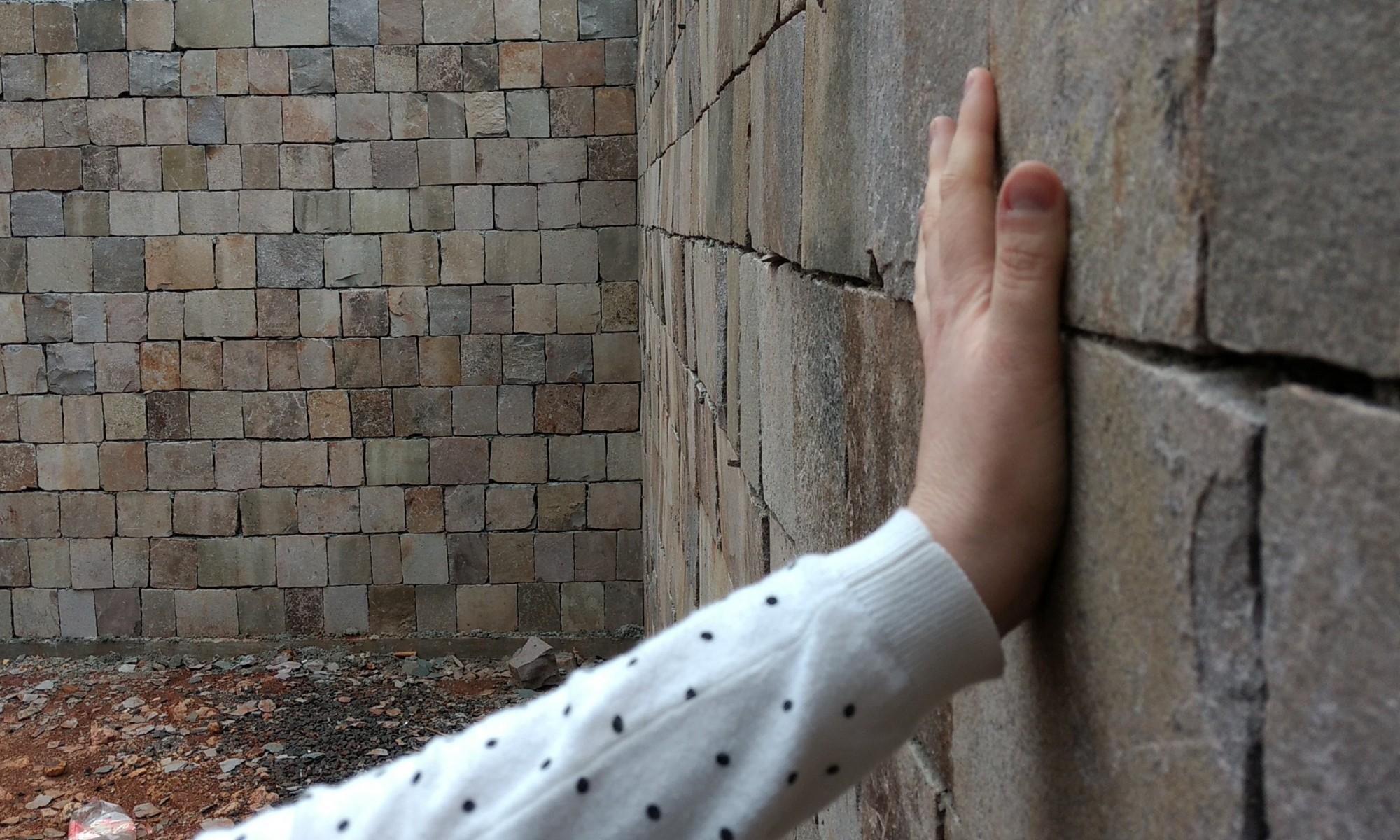 Uma mão apoiada em um muro de pedra, com vários escombros no chão